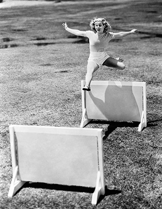 woman jumping hurdles
